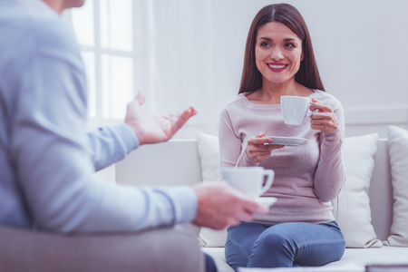 Delighted pretty young woman holding a cup and drinking tea while looking at her friend and smiling broadly