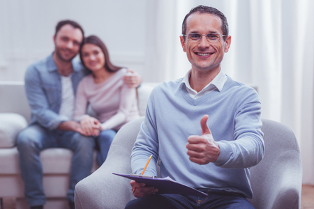 Pleased professional psychologist with glasses keeping his thumb up and smiling broadly while his clients being satisfied with consultation