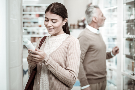 Beaming young woman coming to pharmacy store with her loving father while searching for vitamins