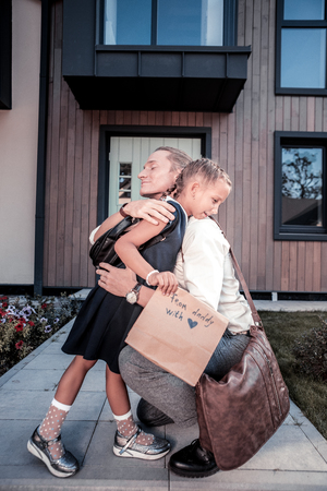 Photo pour Blonde-haired father with brown leather bag hugging his lovely little daughter - image libre de droit