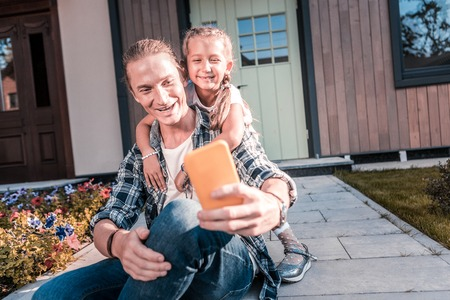 Photo pour Blonde-haired handsome father holding yellow smartphone making selfie with daughter - image libre de droit