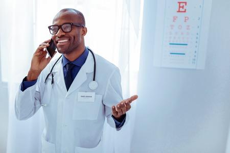 Photo pour Joyful positive man putting phone to his ear while making a call - image libre de droit