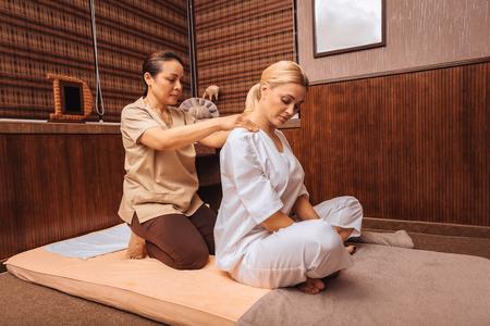 Foto de Relaxing massage. Professional female masseuse standing behind her client while massaging her shoulders - Imagen libre de derechos