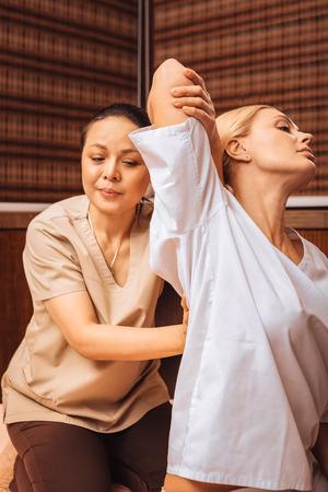 Foto de Salon client. Good looking young woman holding her hand up while having a Thai massage - Imagen libre de derechos