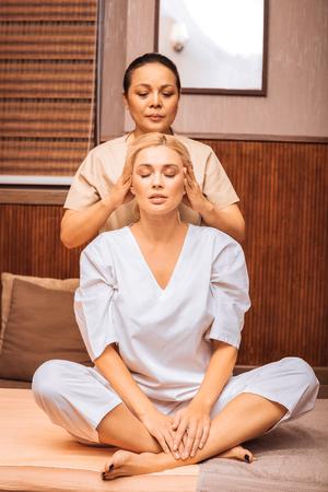 Foto de Absolute relaxation. Nice attractive woman closing her eyes while having a head massage - Imagen libre de derechos