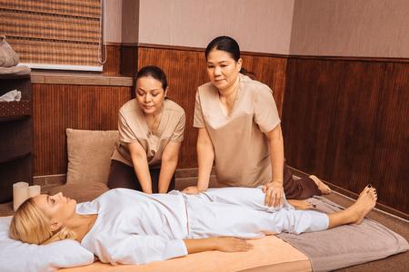Foto de Professional massage salon. Pleasant Asian women having a massage session while working as masseuses in the salon - Imagen libre de derechos