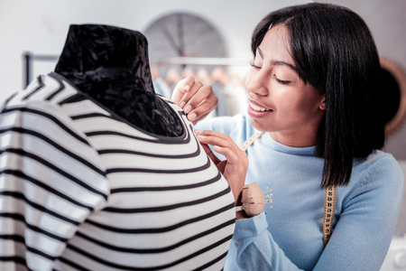 New collection. Portrait of attentive young designer with pins cushion round her wrist taking measurements on mannequins shoulder while expressing interest to work