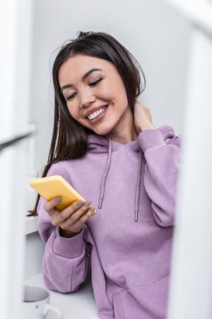 Happy woman. Beaming appealing woman feeling happy receiving message from boyfriend