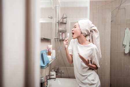 Photo for Like a pop star. Delighted positive woman singing in the bathroom while standing in front of the mirror - Royalty Free Image