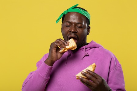 Pleased male person keeping eyes closed while eating sandwich