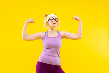 Foto per Showing muscles. Blonde-haired young appealing woman wearing glasses showing her muscles - Immagine Royalty Free