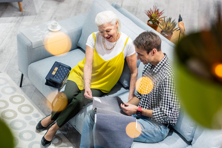 Fancy elderly mother. Stylish joyful dame with grey hair and in fancy bright clothing happily considering textile samples with mature attractive brown-haired son sitting at sofa in the store