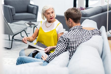 Dame in furniture store. Surprised beautiful white-haired elderly lady wearing bright fashionable outfit choosing textile samples with brown-haired son in store sitting on the sofa