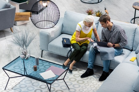 Advising son. Senior stylish grey-haired lady wearing bright yellow top advising nice-looking son in his 30s with selecting furniture in the store