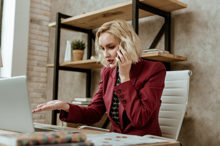 Expressively gesturing. Resolute blonde appealing woman aggressively talking with coworker and pointing on information on laptop screen