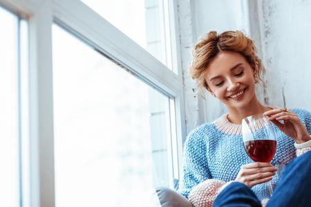 Foto de Favourite drink. Cheerful positive woman smiling while looking at the wine - Imagen libre de derechos