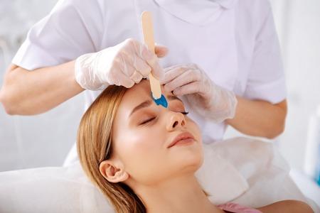 Photo pour Eyebrows correction. Beautiful blonde-haired woman visiting depilatory salon for eyebrows correction - image libre de droit
