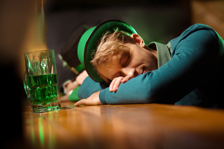 Got drunk. Fair-haired young handsome man wearing a green hat sleeping at the bar counter