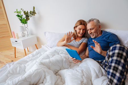 Video chat. Loving mature happy parents having video chat with their daughter using the laptop