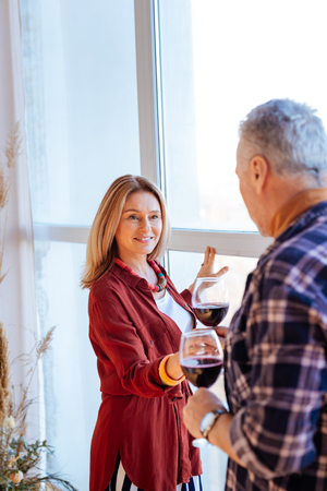 Photo pour Wine from husband. Blonde-haired wife wearing stylish blouse taking glass of red wine from husband - image libre de droit