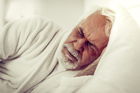 A man in pain. Close-up portrait of an elderly bearded grey-haired wrinkled man in white gown experiencing pain