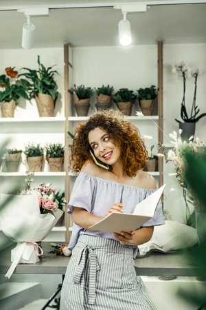 Calling her client. Slim appealing florist feeling a little bit busy while standing in floral shop and calling her client