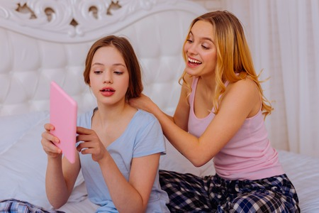 Photo pour Showing dress. Younger sister shopping online and showing the dress while older sister doing hairstyle in bedroom - image libre de droit