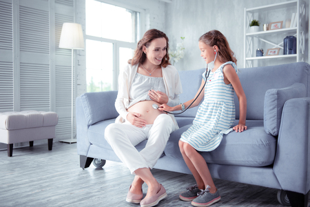 Photo pour Doctor game. Cute little girl feeling involved in playing doctor game with her beautiful pregnant mom - image libre de droit
