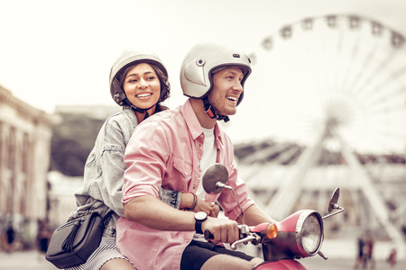Photo pour Positive delighted woman smiling while holding on to her boyfriend - image libre de droit