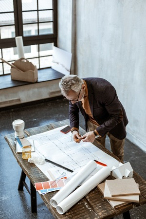 Making some notes. Grey-haired interior designer making some notes on the sketches in his light workshop