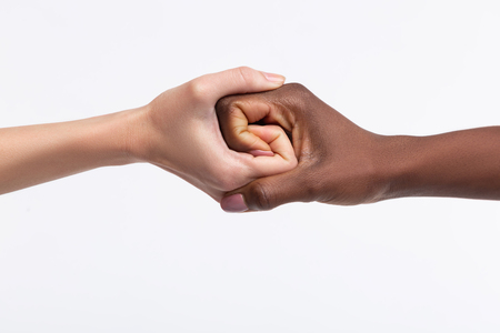 Photo pour Shaking hands. Two women with different skin color shaking their hands while respecting diversity - image libre de droit