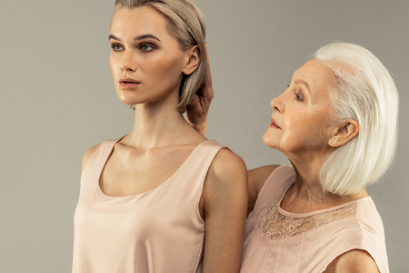 Photo pour Mothers love. Pleasant aged woman touching her daughters hair while standing behind her - image libre de droit