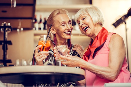 Long-awaiting meeting. Beaming bright women being in great mood while drinking and partying in a bar