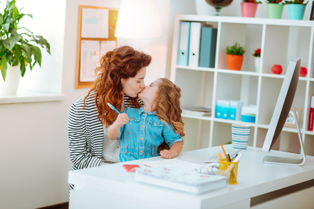 Foto de Mother kiss. Red-haired mother kissing her lovely cute daughter joining her at the working table - Imagen libre de derechos