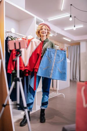 Camera and shopping. Fashionable stylist standing in front of camera while shopping and choosing new outfit