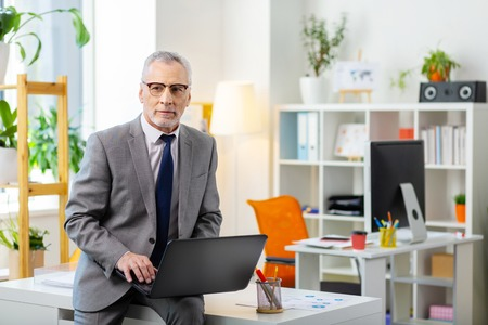 Photo pour Laptop keyboard. Grey-haired man in clear glasses leaning on the table while being alone in the office - image libre de droit