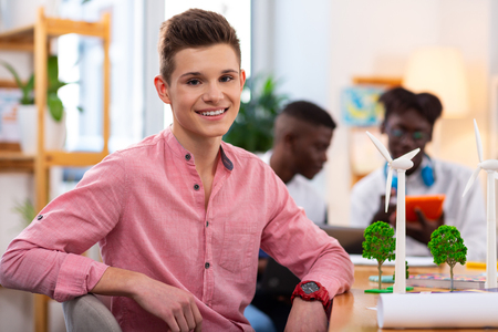 Dark-eyed student. Handsome dark-eyed student wearing red watch sitting at the table after studying with friends