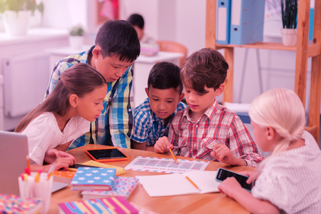 Photo pour Setting up a schedule. Group of concentrated schoolchildren exploring their new timetable together. - image libre de droit