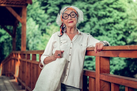 Stylish elderly woman. Attractive joyful beaming fashionable white-haired stylish old lady wearing basic white shirt round-shaped eyeglasses and a bright headband posing on the wooden bridge outdoors