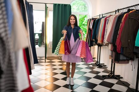 A woman holding packages. Dazzling long-haired charming alluring radiant lovely female of 30s in a lilac dress and cotton jacket holding packages in the clothing store.