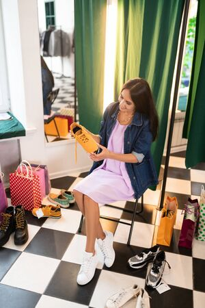Making choice. Happy contended focused cheerful good-looking delightful stylish radiant appealing lady holding a pair of sneakers in hands and selecting the best option