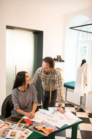 Having conversation. Cheerful contended joyful nice-looking smiling beaming dark-haired designers having a conversation during work at their office