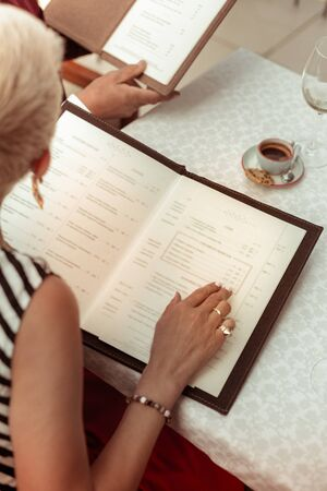 What to order. Top view of mature husband and wife sitting at the table deciding what to order