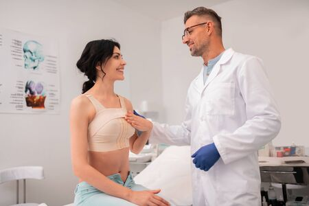 Photo pour Businesswoman having bandage on breast taking to doctor after surgery - image libre de droit