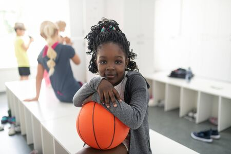 Photo pour Little basketball player. Happy school girl holding her basketball sitting at the bench waiting for her sports lesson. - image libre de droit