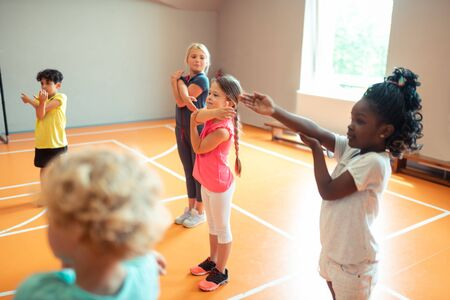 Photo pour Morning at school. Happy elementary school children working out in the gym during their sports lesson. - image libre de droit