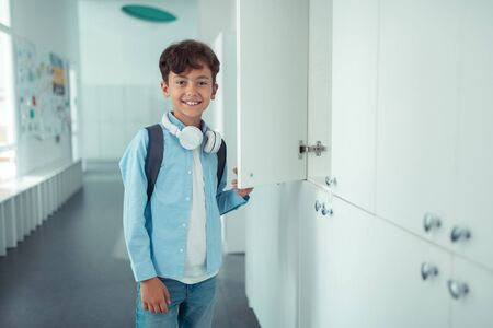 Foto de Handsome schoolboy. Handsome schoolboy wearing earphones on neck smiling while standing near school locker - Imagen libre de derechos
