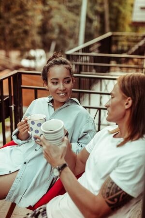 Smiling appealing woman. Pleasant good-looking couple resting together on a balcony and sharing freshly-made tea