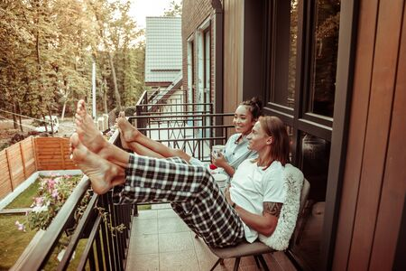 Conversation in the morning. Cheerful friendly couple leaning on the metal railing on a balcony and sipping hot tea from big cups
