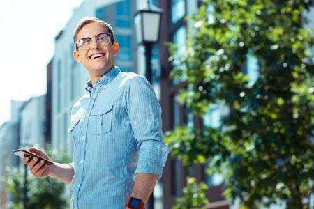 Businessman smiling. Handsome businessman wearing glasses smiling broadly while enjoying weekend walk